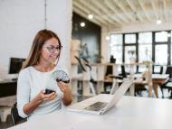 Una mujer se divierte en la oficina con un juguete Slinky frente a un ordenador portátil