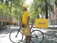 Un repartidor de Glovo junto a su bicicleta de reparto