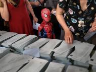 Un niño con un disfraz de Spiderman en una mesa electoral.