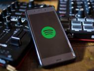 Un móvil con Spotify junto a dos mesas de mezcla de sonido