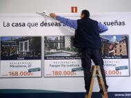 Un operario desmonta un cartel de viviendas en venta en Madrid