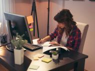 Una trabajadora toma notas ante su ordenador