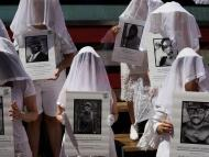 Protesters against gun violence dressed in white clothe hold up photos of the victims of gun violence in Times Square in response to recent mass shootings in El Paso, Texas, and Denton, Ohio, on August 4, 2019, in New York.