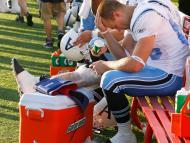Un jugador de fútbol americano se duele de una lesión en la pierna