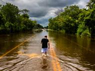 A man walks down a flooded road in Islip, New York in 2014.