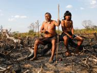 Members of the Xavante tribe sit on charred branches in the Amazon Rainforest.