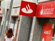 Una mujer pasa por delante de una oficina de Banco Santander y Banco Popular.