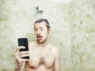 Un hombre usa el móvil en la ducha