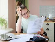 Una joven revisa facturas con un ordenador y una calculadora