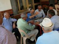 Un grupo de jubilados juega una partida de dominó en una terraza en Fuengirola (Málaga)