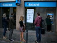 Varios clientes hacen cola ante un cajero automático del Banco Sabadell