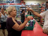 "A woman uses her ""mumbuca"" card at a pharmacy in Marica, Brazil."