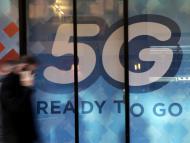 Un hombre camina delante de un cartel de 5G