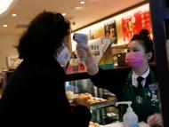 Una camarera mide la temperatura de una clienta en una cafetería Starbucks en Pekín
