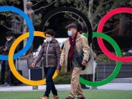 Dos japoneses caminan frente al logo de los Juegos Olímpicos de Tokio en pleno brote por el coronavirus.