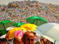Muslim pilgrims carrying umbrellas to block the sun.