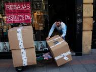 Un trabajador introduce unas cajas de mercancía en una tienda de ropa de Madrid