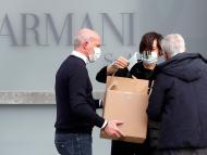 Trabajadores reparten mascarillas a las puertas del teatro donde Giorgio Armani tenía previsto realizar su desfile de la semana de la moda de Milán.