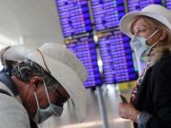 Unos turistas con mascarilla esperan información de vuelo en el aeropuerto de El Prat