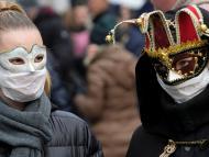 2 asistentes al Carnaval de Venecia con mascarillas sanitarias debajo de sus máscaras