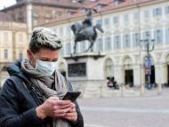 Una mujer mira su móvil durante el brote de coronavirus en Turín, Italia.