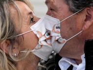 Dos personas con mascarillas besándose