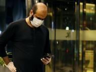 Un hombre con mascarilla y guantes consulta su app de coronavirus.
