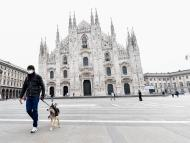 Un hombre pasea a su perro en la plaza del Duomo