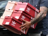 Un hombre con varias cajas de zapatillas de Adidas en Berlín