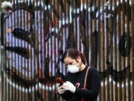 Una mujer consulta su teléfono móvil durante el confinamiento por el coronavirus