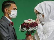 Palestinian groom Mohamed abu Daga and his bride Israa wear protective masks amid the COVID-19 epidemic, during a photoshoot at a studio before their wedding ceremony.