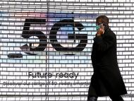 A pedestrian walks past an advertisement promoting the 5G data network at a mobile phone store in London in January 2020.