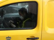 Trabajador de Correos mira su móvil durante la epidemia de coronavirus.
