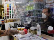 Un cliente saluda al dependiente de una tienda de pintura en Madrid