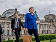 German Chancellor Angela Merkel walks with her bodyguards in Berlin, May 13, 2020.