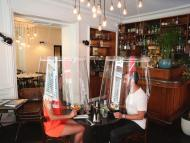 A man and a woman demonstrate dining under a plastic shield Wednesday, May 27, 2020 in a restaurant of Paris. As restaurants in food-loving France prepare to reopen, some are investing in lampshade-like plastic shields to protect