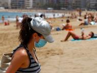 Una mujer con mascarilla en la playa de Las Canteras de Gran Canaria