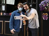 People wearing protective masks pose for a selfie during the coronavirus pandemic on May 27, 2020 in New York City.