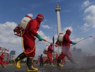 Un grupo de bomberos con trajes protectores desinfecta una zona turística en Jakarta pare frenar la propagación del coronavirus