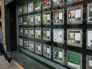 Un hombre con mascarilla mira ofertas de pisos en una inmobiliaria de El Masnou (Barcelona)