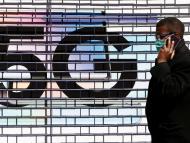 Un hombre con mascarilla pasa delante de un anuncio de 5G durante el coronavirus.