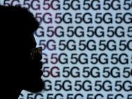 Un hombre pasa delante de un anuncio de 5G en Londres.