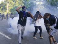 Manifestantes huyen del gas lacrimógeno utilizado por la policía estadounidense