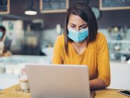 mujer con mascarilla mirando el ordenador