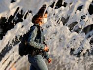 Una mujer pasea con una mascarilla en medio de la crisis del coronavirus