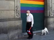 Un jubilado con mascarilla pasea a su perro en Barcelona