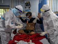 Unos médicos vestidos con trajes de protección examinan a un enfermo de COVID-19