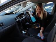 Una mujer limpia el interior de su coche