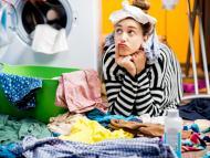 Mujer rodeada de ropa para lavar.