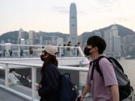 Personas con mascarillas caminan frente a los rascacielos de Hong Kong.